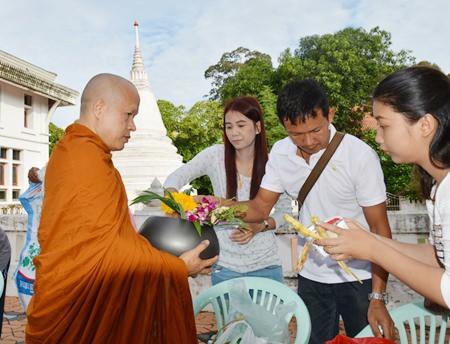 The Theerarak family makes merit at Wat Chong Lom in Naklua.