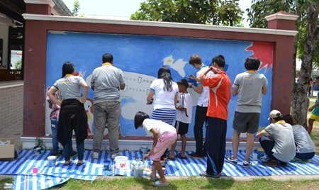 This group helps children paint a mural of a huge airplane on the Benefactors Wall.