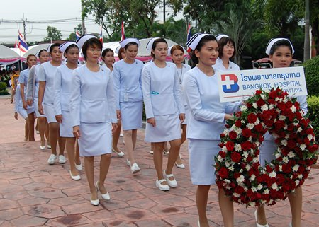 Nurse from Bangkok Hospital Pattaya bring carry a wreath to lay in front of the Rama V monument in Banglamung.
