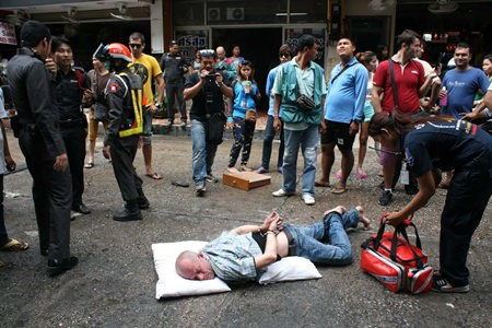 Denis Wieslaw Leszek remains handcuffed on the ground after going into a manic rage on Soi 6.