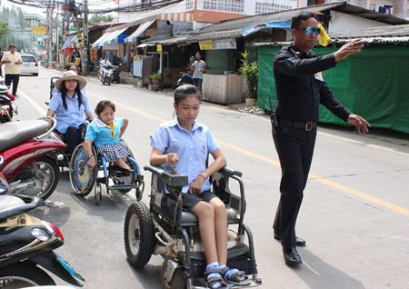 In this case, in front of the press, a friendly traffic officer helps wheelchair users negotiate motorcycles parked in the wheelchair path as city officials and police inspect the area (in the background).