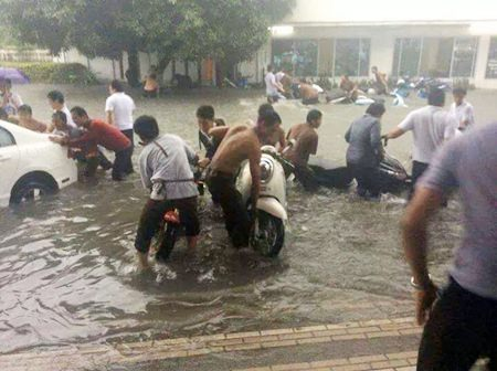 Residents in the Boontaworn area on Sukhumvit struggle to get their cars and motorbikes out of the floods.