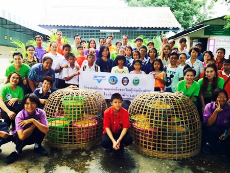 YWCA Chairwoman Praichit Jetpai (standing, 3rd left) along with YWCA members and guests teach students and teachers at Pattaya School No. 7 how to grow mushrooms.