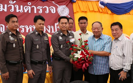 Nongprue Mayor Mai Chaiyanit (2nd right) presents a congratulations basket to Nongprue Police Station Superintendent Col. Suthisak Wanthee on National Police Day.