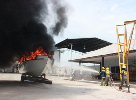 Firefighters work to extinguish the suspicious fire aboard this multi-million baht boat.
