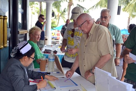 The PCEC arranged with Phyathai Sriracha Hospital to administer flu shots during the Club's Sunday meeting. Here club member Les Edmonds is locating his name on the signup sheet for the nurse.