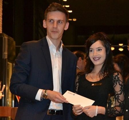 Adam Sutcliffe, sales director for Thailand-proerty.com hands over a hotel voucher to the lucky winner.