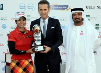 Thailand's Pornanong Phatlum (left) is shown receiving the 2013 winner's trophy from Raynald Aeschlimann, vice president, International Sales Director of Omega, as Mohamed Juma Buamaim, vice chairman and CEO of golf in DUBAi, looks on.