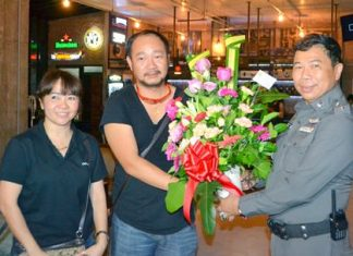 Pol. Col. Dhamnoon Munkong (right), Superintendent of the Banglamung Police Station, presents flowers to the management team of Café de Beach during the soft opening ceremony.