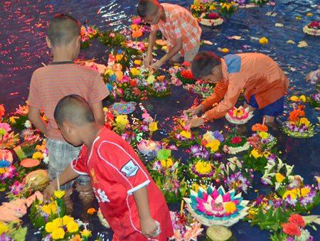 Children look for money from inside the krathongs.