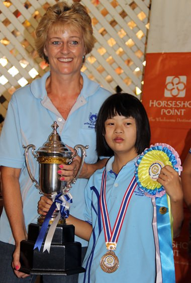 Miss Ploy, winner of the walk category, receives the winner's trophy from Sandra Cooper.