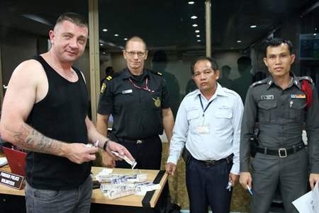 Taxi driver Kamsin Meethongsan returns the lost money and passport to British tourist David Pennington.