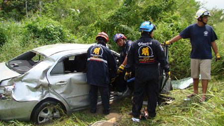 Experts work to extricate the victims after their car was struck by a State Railway of Thailand train at an unmarked crossing in Nong Sadao in Banglamung District.