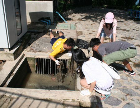 Students dig deep to clean the drains.