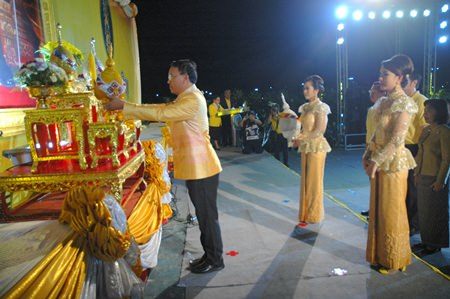 Apichart Thepnoo, Chief Judge of the Pattaya Provincial Court, places gold and silver floral ornaments in front of His Majesty's portrait at Bali Hai Pier.