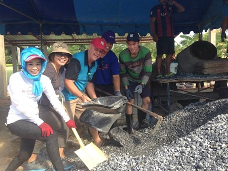 Praichit Jetpai (left), president of the YWCA Bangkok-Pattaya, and volunteers take part in mixing the concrete for the building.