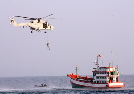 The Royal Thai Navy practices rescuing an unconscious fisherman by airlifting him via helicopter.