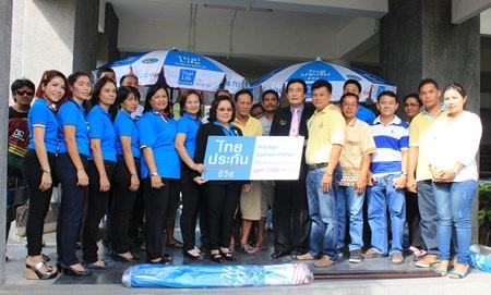 Samran Topao, sales manager for Thai Life Insurance Company, and his management team presents 3,000 umbrellas worth 3 million baht to Deputy Mayor Ronakit Ekasingh to distribute to Jomtien Beach vendors.