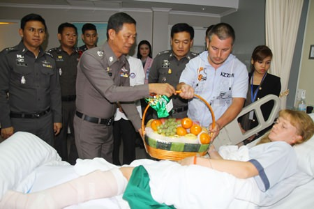 Police and representatives from the Pattaya Tourist Assistance Fund visit the Russian woman in the hospital and present her with 20,000 baht and a fruit basket.