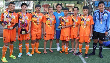 Shai Davis (centre) poses with the Banglamung Boys Home – the tournament winning team.