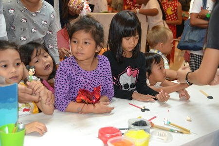 Youngsters prepare for the coloring books to be brought out in the coloring booths at Central Festival Pattaya Beach.