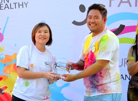 TAT Pattaya Director Suladda Sarutilavan (left) presents a prize to a runner from Bangkok who heard about the Colour Run via Facebook
