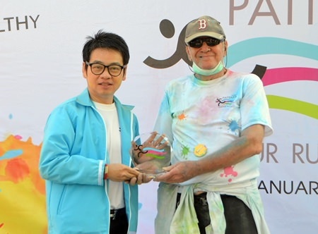 Chairman of Tourism & Sports Rattanachai Sutidechanai presents a trophy to Donald Maclaughlin (right) aged 76 the winner of the oldest runner prize.