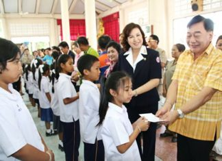 Permanent Secretary Phawat Lertmukda (right) hands out scholarships to Sattahip students as part of Chonburi Provincial Administrative Organization's efforts to reach out to rural residents.