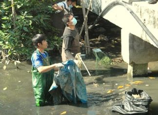 Volunteers clean out garbage, leaves, broken branches and other obstructions to water flow from Nok Yang Canal in Naklua.