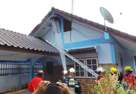 Firefighters extinguish a small fire that damaged an empty home in Sattahip.