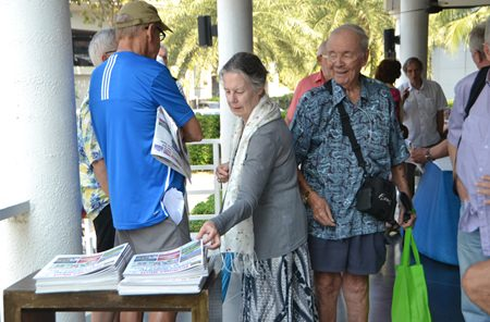 Attendees at the PCEC Sunday meeting pick up their free copy of Pattaya Mail, which is available at the end of the meeting.
