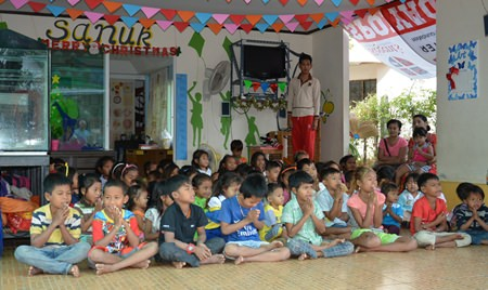 Children at the Sanuk Day Care Center sit and watch intently during the presentation of an afternoon of traditional Thai dance.