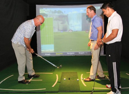 """Centara's George Kenton (left), Executive Assistant Manager Rooms Division together with Marut Jansud, Leisure Manager (right) and Bruce Whitehead (centre), PGA Professional, test the new arrival of the Xcite """"Golf Simulator"""" at the Centara Grand Mirage Beach Resort in Pattaya."""