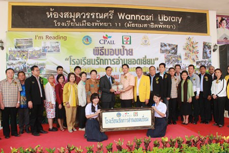 "Suwit Kingkaew (center left), senior vice president of CP All Plc., presents Pattaya's first ""Love to Read School"" sign to Mayor Itthiphol Kunplome (center right) and other officials representing Pattaya School No. 11."
