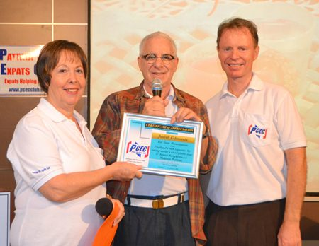 MC Richard Silverberg presents the PCEC's Certificate of Appreciation for their sharing the scenic beauty and interesting sights of recent trips to three provinces in Thailand.