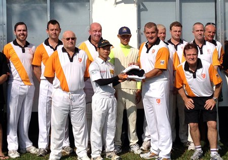 PCC captain Simon Philbrook (6th right) presents club shirts, shorts and caps to sponsored cricketers Thanchai and Cher.