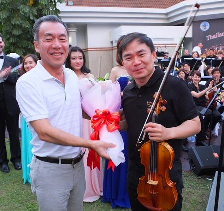 Masaya Furuta, Vice-President of Yamaha presents flowers to concert-master Sittichai Pengcharoen.