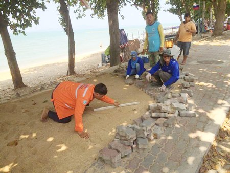 City workers filled in a 10-meter-long hole and built a cement retaining wall to prevent erosion, then laid bricks to complete the path at Yim Yom Beach.