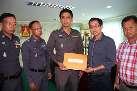 Kantapon Sukumalin hands his complaint over to Pattaya police superintendent Pol. Col. Sukthat Pumpunmuang.