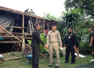 Officials inspect the damage as soldiers begin to repair a damaged roof on Koh Chan.