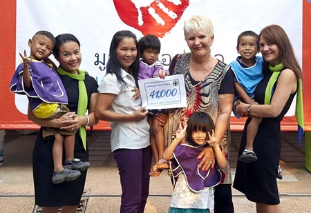 Eva Johnson (centre right), a co-founder of the Pattaya Soul Club, and flanked by Min (far left) and Janey (far right) of the Riviera Group, presents a cheque for 41,000 baht to Kh. Pai, the President of the Hand to Hand Foundation (centre left) along with children under the care of the organisation.