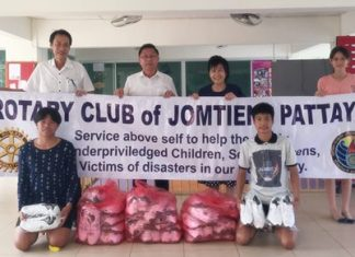 Rotary Club of Jomtien-Pattaya President Vutikorn Kamolchote (left) hands over the donated shoes to Pastor Praison of the RPB Church in Laem Chabang.
