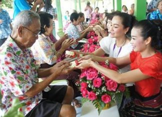"YWCA Chairwoman Praichit Jetapai (right) and YWCA members take part in the traditional ""rod nam dam hua"" ceremony at the Banglamung Home for the Elderly."