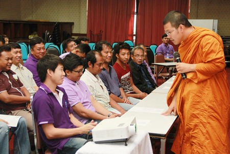 Pra Ajarn Mahachanchai (right) talks to city workers about ethics and moral development.