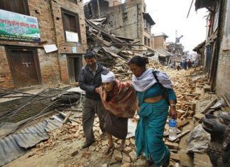 An elderly injured woman is taken to her home after treatment in Bhaktapur near Kathmandu, Nepal, Sunday, April 26. A strong magnitude 7.8 earthquake shook Nepal's capital and the densely populated Kathmandu Valley before noon Saturday, April 25, causing extensive damage with toppled walls and collapsed buildings, officials said. (AP Photo/Niranjan Shrestha)