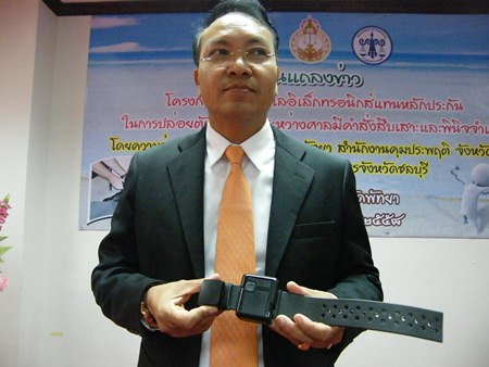 Chief Justice Apichart Thepnoo presents one of the GPS tracking bracelets.