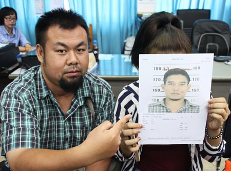 Reporter Klitichai Sapaklit points to a photo of Hathapong Hintua, wanted for sexual harassment of his girlfriend (holding photo).