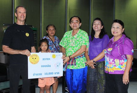 Jesters Chairman Lewis Underwood presents a 10,000 baht donation to Nongprue Deputy Mayor Enake Pathanangam to be used to build a new bathroom for Pemika's family.