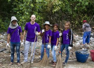 Volunteers from MAYs Urban Thai Dine Pattaya grab rakes and brooms to help clean up the litter.