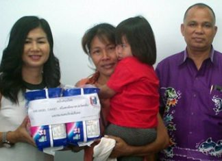 PSC Charity Chairwoman Noi Emmerson (left) leads the handover of 50,000 baht to Nongprue Sub-district for milk, eggs, diapers and other staples for families with special-needs children.